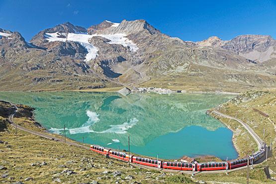 Eindrückliche Panorama-Fahrt über die höchste Bahntransversale der Alpen, hinauf zum Gletscherglitzern der Berge und hinab ins Palmenparadies Italiens.